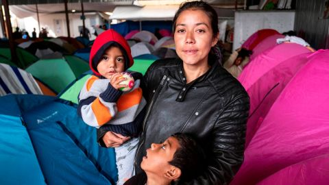 """Gabriela Hernandez and her children Jhonnathan and Omar, Central American migrants traveling in the """"Migrant Via Crucis"""" caravan stand for a portrait outside near their tent at Juventud 2000 shelter   in Tijuana, Baja California state, Mexico, on April 27, 2018."""