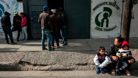 """Gabriela Hernandez and her children Jhonnathan and Omar, Central American migrants traveling in the """"Migrant Via Crucis"""" caravan sit outside Juventud 2000 shelter   in Tijuana, Baja California state, Mexico, on April 27, 2018."""