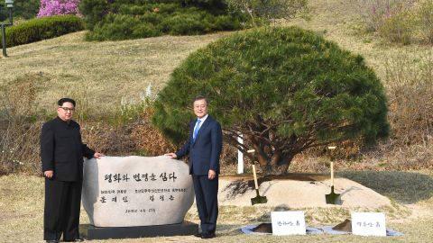"""North Korea's leader Kim Jong Un (L) and South Korea's President Moon Jae-in (R) pose in front of a stone inscribed """"Peace and Prosperity Are Planted"""" as they participate in a tree-planting ceremony next to the Military Demarcation Line that forms the border between the two Koreas at the truce village of Panmunjom on April 27, 2018. - North Korean leader Kim Jong Un and the South's President Moon Jae-in sat down to a historic summit on April 27 after shaking hands over the Military Demarcation Line that divides their countries in a gesture laden with symbolism. (Photo by Korea Summit Press Pool / Korea Summit Press Pool / AFP)        (Photo credit should read KOREA SUMMIT PRESS POOL/AFP/Getty Images)"""