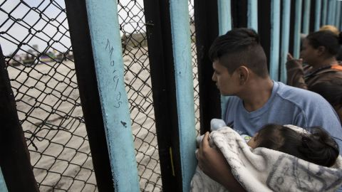 A member of the Central American migrant caravan, holding a child, looks through the border wall toward a group of people gathered on the U.S. side, as he stands on the beach where the border wall ends in the ocean, in Tijuana, Mexico, Sunday, April 29, 2018. U.S. immigration lawyers are telling Central Americans in a caravan of asylum-seekers that traveled through Mexico to the border with San Diego that they face possible separation from their children and detention for many months. They say they want to prepare them for the worst possible outcome. (AP Photo/Hans-Maximo Musielik)