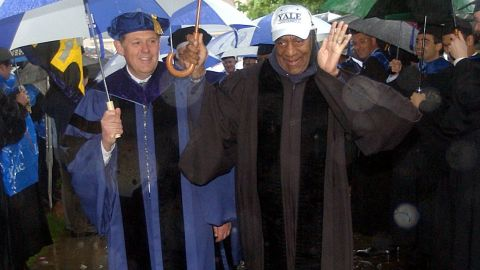 Bill Cosby, center right, waves to graduates as he walks in a rain-soaked academic procession on Yale University campus in New Haven, Conn., Monday, May 26, 2003, on the way to commencement ceremonies. Cosby was awarded an honorary Doctor of Humane Letters degree by Yale during the rain-shortened ceremony. (AP Photo/Bob Child)