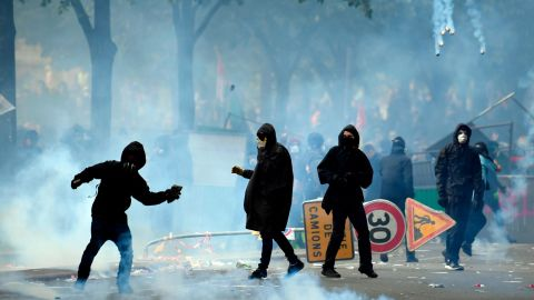 A protestor throws a stone towards police officials as teargas clouds rise during a demonstration on the sidelines of a march for the annual May Day rally in Paris.