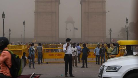 An Indian traffic policeman covers his face as he stands on duty in New Delhi.