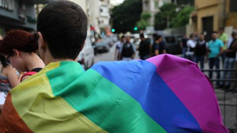 A protester covers his back with a rainbow flag during a sit-in to protest the ongoing criminalization of homosexuality and arbitrary arrests, in front of Hobeich Police Station, where protesters say four men are being held for homosexuality, in Beirut, Lebanon, Sunday, May 15, 2016. (AP Photo/Hussein Malla)