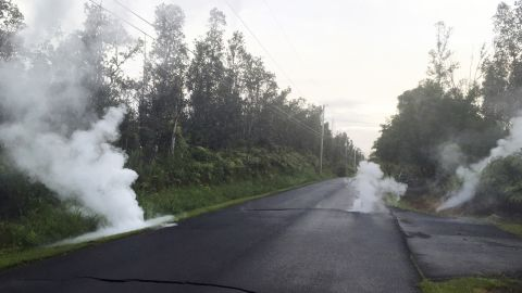 In this image released by the U.S. Geological Survey, steam rises from cracks in the road shortly before a fissure opened up on Kaupili Street in the Leilani Estates subdivision, Friday, May 4, 2018, in Pahoa, Hawaii. The Kilauea volcano sent more lava into Hawaii communities Friday, a day after forcing more than 1,500 people to flee from their mountainside homes, and authorities detected high levels of sulfur gas that could threaten the elderly and people with breathing problems.  (U.S. Geological Survey via AP)