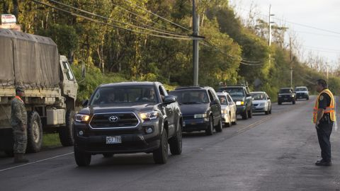 As authorities watch,  Leilani Estates residents line up on the road leading to the area.