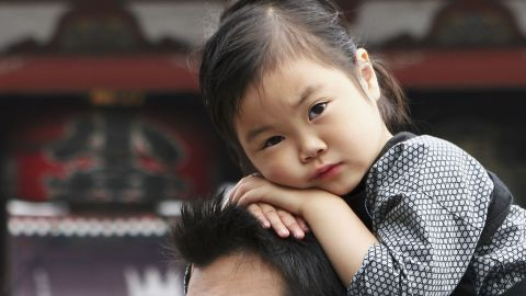 TOKYO, JAPAN - MAY 22:  A Japanese girl sits on her fathers shoulders during the annual Sanja Festival at Tokyo's Sensoji Temple on May 22, 2005 in Tokyo, Japan. Sanja Matsuri is one of the three biggest Summer festivals in Tokyo and has been continued from the Edo period. (Photo by Koichi Kamoshida/Getty Images)