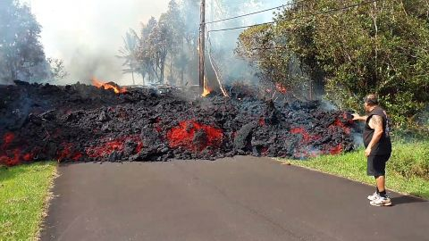 In this photo taken from video an unidentified man gets close to a lava flow advancing down a road in the Leilani Estates subdivision near Pahoa on the island of Hawaii Monday, May 7, 2018. Kilauea volcano has destroyed more than two dozen homes since it began spewing lava hundreds of feet into the air last week, and residents who evacuated don't know how long they might be displaced. The decimated homes were in the Leilani Estates subdivision, where molten rock, toxic gas and steam have been bursting through openings in the ground created by the volcano. (Scott Wiggers/Apau Hawaii Tours via AP)