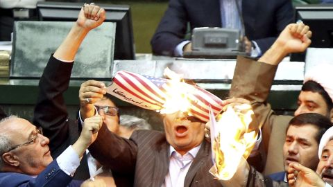 """Iranian lawmakers burn two pieces of papers representing the U.S. flag and the nuclear deal as they chant slogans against the U.S. at the parliament in Tehran, Iran, Wednesday, May 9, 2018. Iranian lawmakers have set a paper U.S. flag ablaze at parliament after President Donald Trump's nuclear deal pullout, shouting, """"Death to America!"""". President Donald Trump withdrew the U.S. from the deal on Tuesday and restored harsh sanctions against Iran. (AP Photo)"""
