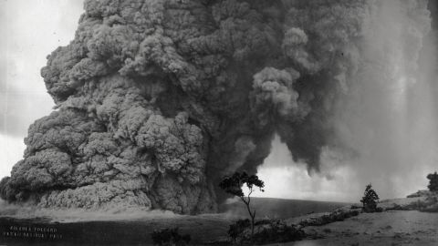"""Kilauea Volcano, Hawaii National Park [No information was provided about this print but the print is identical to a print found in the Lovejoy family photograph album at the national park archives. That copy of the print had a notation as follows:  """" 389 Apri-May 1924 Eruption. Halemaumau Crater which lies within an outer crater called Kilauea. The trees in this picture are three miles from Halemaumau. Boulders as large as 14 tons were tossed in the air. Most were smaller- many from three to seven tons. Small green stones called olivines are found in the boulders and when polished are quite pretty. Also known as Hawaiian diamonds.   Copyright K. Maehara.""""  This is almost certainly a photo taken by Maehara at Uwekahuna bluff at about 11:15 on May 18, 1924.  The image is very similar to other photos taken by Maehara from the bluff at that time on that date.   The image shows almost the exact moment when Truman Taylor was killed by this explosive blast.]"""