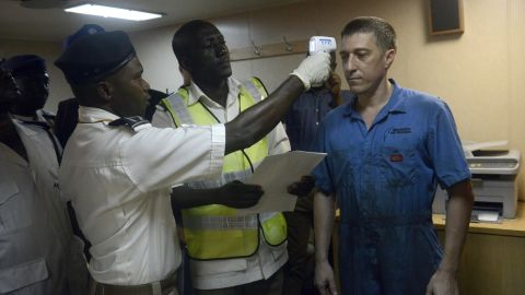 """Health officials take the body temperature of an Ukrainian sailor on the MV Pintail ship, as they check for signs of the Ebola virus at the Apapa Sea Port, in Lagos, on September 29, 2014. Health officials have begun the screening of cargo ship crews transiting through the ports of Nigeria to prevent cross border transmission of Ebola through sea and cargo ports. Nigeria has cleared all patients under surveillance for the Ebola virus, the federal health ministry said on September 24, 2014. """"There is nobody again under surveillance for the Ebola virus in any part of Nigeria. All those under surveillance have completed their mandatory 21-day period stipulated by the WHO,"""" ministry's spokesman Dan Nwomeh told AFP, referring to the World Health Organization.  PHOTO/PIUS UTOMI EKPEI        (Photo credit should read PIUS UTOMI EKPEI/AFP/Getty Images)"""