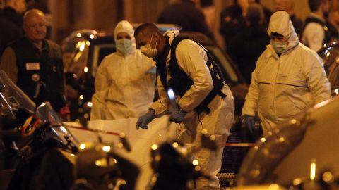 Investigators look through the scene of the attack Saturday night.