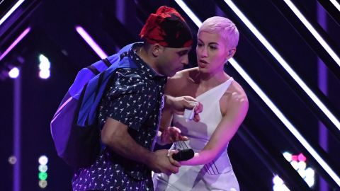A protester grabs the microphone from Britain's singer, SuRie.