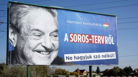 """A billboard with a poster of Hungarian-American billionaire and philanthropist George Soros with the lettering """"National consultation about the Soros' plan - Don't let it pass without any words"""" is seen in the 22nd district of Budapest on October 16, 2017, as the conservative government prepares their new national consultation.Since 2013, once one of Europe's most far-right parties Jobbik, whose members burned EU flags and called Jewish lawmakers a national security risk, has been lurching toward the political centre. And as Hungary readies for an election on April 8 Jobbik, which polls show is the strongest party behind Prime Minister Viktor Orban's ruling Fidesz, claims it is ready for government. An expert on the Hungarian far-right Peter Kreko says Orban's sharpening edge has forced Jobbik, who have criticised his relentless attacks on Soros and civil society groups, toward the centre. / AFP PHOTO / ATTILA KISBENEDEK        (Photo credit should read ATTILA KISBENEDEK/AFP/Getty Images)"""