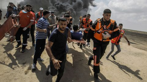 Medical units carry away a wounded Palestinian shot by Israeli forces during a protest on the border fence separating Israel and Gaza on Monday.