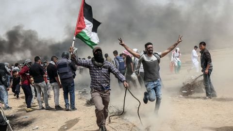 """TOPSHOT - Palestinian protesters pull a metal cable as they try to take down a section of barbed wire during clashes with Israeli forces on April 20, 2018, east of Khan Yunis, in the southern Gaza Strip during mass protests along the border of the Palestinian enclave, dubbed """"The Great March of Return,"""" which has the backing of Gaza's Islamist rulers Hamas. (Photo by SAID KHATIB / AFP)        (Photo credit should read SAID KHATIB/AFP/Getty Images)"""