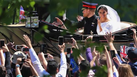 Well-wishers take pictures as Harry and Meghan pass in their carriage.