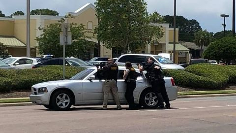Authorities have weapons drawn in a photo provided by Stacie Houchins.
