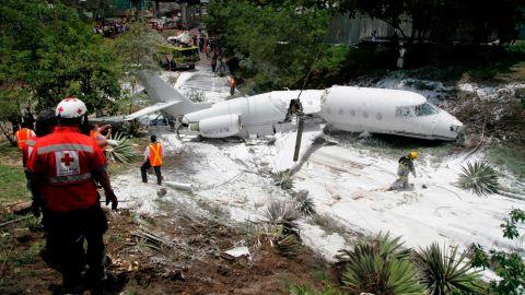 Broken in half, the jet lies engulfed in foam sprayed by Honduran firefighters.