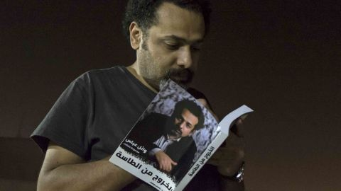 """Prominent activist and blogger Wael Abbas signs a copy of his book, """"The Theory of Leaving the Bowl,"""" in Cairo."""