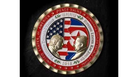 """A commemorative coin featuring US President Donald Trump and North Korea's Kim Jong Un was struck by the White House Communications Agency ahead of their summit meeting, which Trump has cancelled. The coin depicts Trump and Kim, described as North Korea's """"Supreme Leader,"""" in profile facing each other in front of a background of US and North Korean flags."""