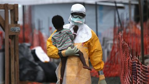 PAYNESVILLE, LIBERIA - OCTOBER 05:  A Doctors Without Borders (MSF), health worker in protective clothing carries a child suspected of having Ebola in the MSF treatment center on October 5, 2014 in Paynesville, Liberia. The girl and her mother, showing symptoms of the deadly disease, were awaiting test results for the virus. The Ebola epidemic has killed more than 3,400 people in West Africa, according to the World Health Organization.  (Photo by John Moore/Getty Images)