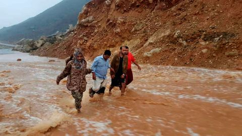 Men walk on a flooded road Thursday as rain and winds from Cyclone Mekunu hit  the island of Socotra.