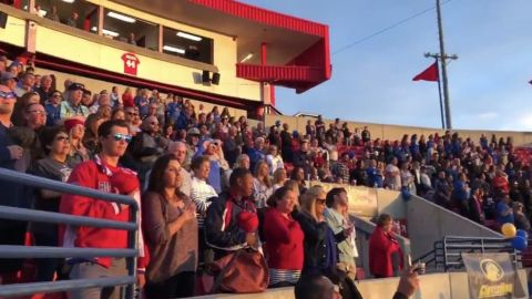 Fans stand for the National Anthem before a softball game on Friday in Clovis, California