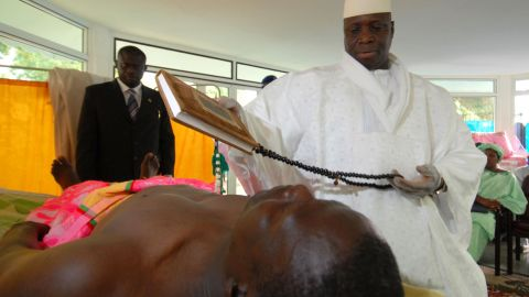 Gambian President Yahya Jammeh prays while administering his alleged herbal HIV cure to a patient at the State House in Banjul on February 15, 2007.