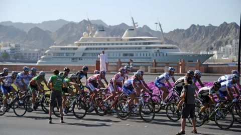 """Cyclists ride past the Sultan of Oman's yacht  Al Said during the Tour of Oman race in 2011. The superyacht reportedly has space for <a href=""""http://uk.businessinsider.com/expensive-luxury-yachts-2018-3/#300-million-the-sultan-of-oman-owns-the-509-foot-long-al-said-yacht-it-has-room-for-more-than-60-guests-and-a-concert-hall-that-can-house-a-50-piece-orchestra-6"""" target=""""_blank"""" target=""""_blank"""">a concert hall equipped for a 60-piece orchestra. </a>"""