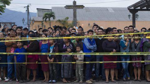 Neighbors stand outside a temporary morgue near Volcan de Fuego in Alotenango, Guatemala.