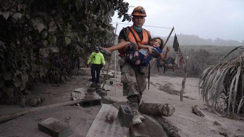 A rescue worker carries a girl in El Rodeo, Escuintla.