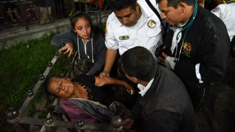 A woman is cared for by firefighters after she learned that a relative was among the victims in Alotenango.