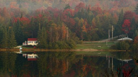 Leaves begin turning color in the early morning mist 06 October 2007 as houses and trees are reflected on Big Pond near Woodford, Vermont. Fall foliage in the New England region is reaching its peak this week.          AFP PHOTO/Stan HONDA (Photo credit should read STAN HONDA/AFP/Getty Images)