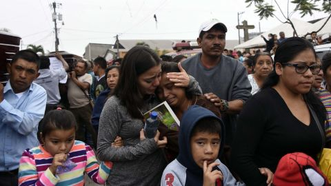 Women mourn as coffins of the volcano's dead are carried Monday along the streets of Alotenango.