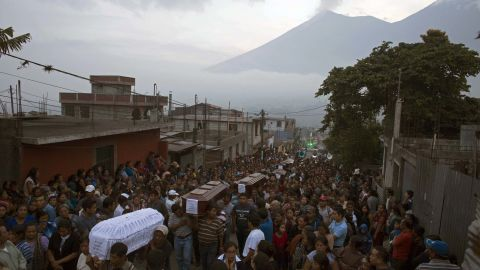 People carry the coffins of seven people who died during the eruption of the Volcan de Fuego, which in Spanish means Volcano of Fire, in the background, to the cemetery in San Juan Alotenango, Guatemala, Monday, June 4, 2018. Residents of villages skirting the volcano began mourning the dead after an eruption buried them in searing ash and mud. (AP Photo/Luis Soto)
