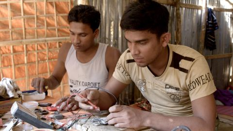 Anowar, right, mends cellphones in Kutupalong refugee camp in Bangladesh.