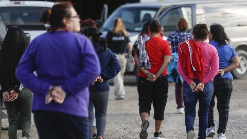 Government agents lead suspects in custody toward a restroom during an immigration sting at Corso's Flower and Garden Center on Tuesday in Castalia, Ohio.