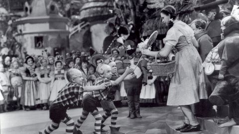 Jerry Maren, center, playing a Lollipop Guild Member, presents Judy Garland with a lollipop in the film 'The Wizard of Oz.'