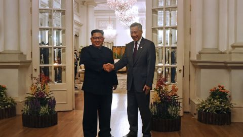 """North Korea's leader Kim Jong Un (L) is welcomed by Singapore's Prime Minister Lee Hsien Loong (R) during his visit to The Istana, the official residence of the prime minister, following Kim's arrival in Singapore on June 10, 2018. - Kim Jong Un and Donald Trump will meet on June 12 for an unprecedented summit in an attempt to address the last festering legacy of the Cold War, with the US president calling it a """"one time shot"""" at peace. (Photo by ROSLAN RAHMAN / AFP)"""
