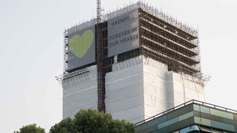 """A banner reading """"Grenfell Forever in our Hearts"""" hangs over scaffolding at Grenfell Tower on June 6, 2018."""