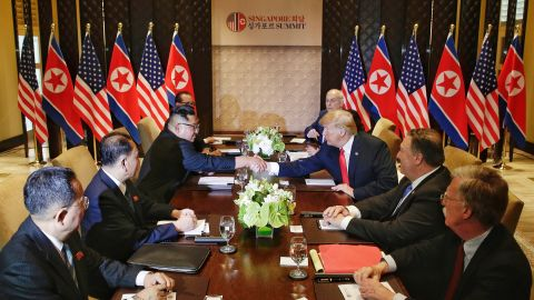 US President Donald Trump (3rd R) shakes hands with North Korea's leader Kim Jong Un (3rd L) as they sit down with their respective delegations for the US-North Korea summit, at the Capella Hotel on Sentosa island in Singapore on June 12, 2018.]