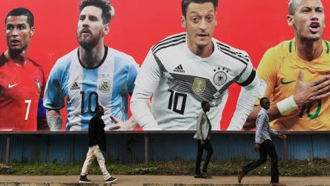 People walk past a football billboard displaying (From L) Portugal's forward Cristiano Ronaldo, Argentina's forward Lionel Messi, Germany's midfielder Mesut Ozil and Brazil's striker Neymar on June 9, 2018 in Nairobi, ahead of the Russia 2018 World Cup. (Photo by SIMON MAINA / AFP)        (Photo credit should read SIMON MAINA/AFP/Getty Images)