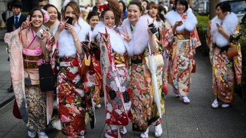 YOKOHAMA, JAPAN - JANUARY 08:  Women wearing kimonos gesture at the camera as they leave after attending a Coming of Age ceremony on January 8, 2018 in Yokohama, Japan. Coming of Age Day is a Japanese holiday held every January to celebrate people who have reached 20 - the official age of adulthood in Japan. Yokohama city, with almost 37,000 people turning 20 this year, is holding one of the largest events in the country.  (Photo by Carl Court/Getty Images,)