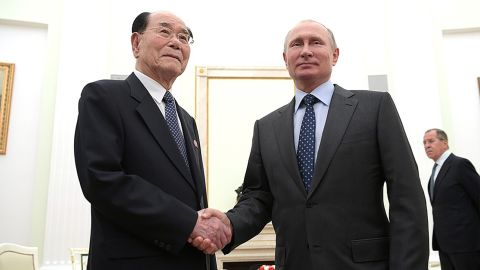 Russian President Vladimir Putin and  senior North Korean official Kim Yong-nam shake hands in Moscow