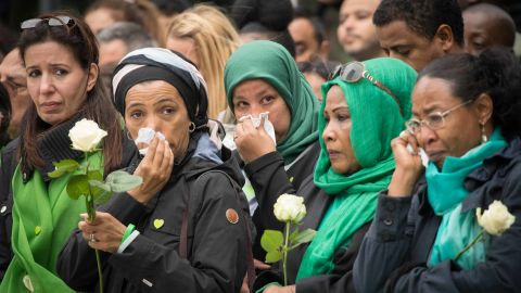 Families of victims of the Grenfell Tower disaster attend a service at the base of the burned-out apartment block on  Thursday.