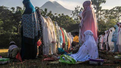 With Mount Merapi in the background, women perform Eid prayers in Yogyakarta, Indonesia.