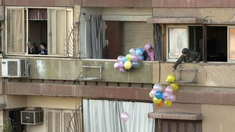 People throw balloons to passers-by in Cairo.