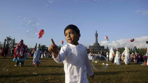 A boy plays with bubbles during Eid al-Fitr prayers in Bali, Indonesia.