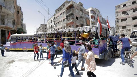 "People ride a ""fun train"" on the war-damaged streets of Douma, Syria."